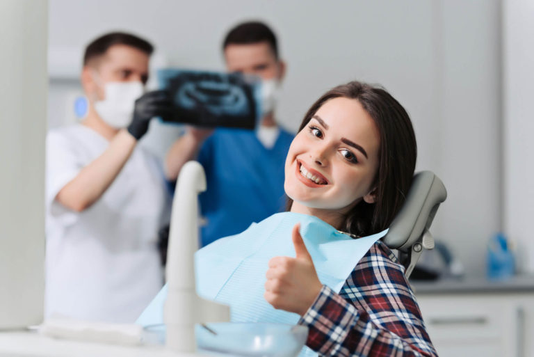 Girl in chair at dental surgery giving the thumbs up